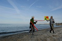 Two mature women flying a kite at Baltic Sea beach