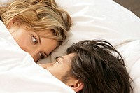 Young couple lying in a bed, face to face