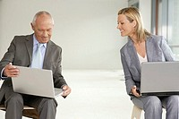 Elderly manager and business woman sitting on stools, laptops on their knees