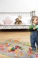 Baby boy standing on a play carpet