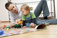 Father and son playing on play carpet