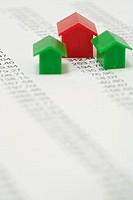 Three plastic miniature-houses standing on a financial paper, selective focus