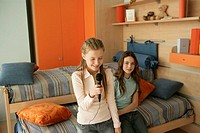 Two friends sitting on a bed, one girl singing