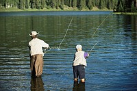 Father and son fly fishing, rear view
