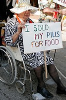 Annual satire parade, parody, senior, wheelchair, sold pills for food. King Mango Strut. Coconut Grove. Florida. USA.