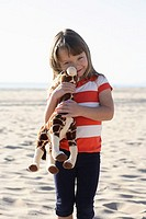 Girl on Beach Holding Stuffed Giraffe