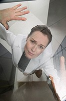 Businesswoman pressing against a glass ceiling, portrait
