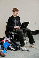 Adult businessman professional works on wireless laptop computer while traveling outside of the office
