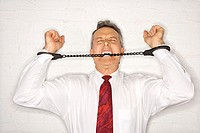 Angry Businessman Biting Handcuffs