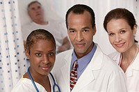Group of doctors in hospital with patient behind.