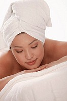 Asian woman with towels at spa, eyes closed.