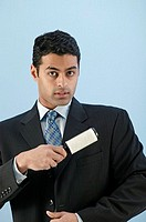 Businessman using lint brush, portrait.
