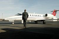 Businessman getting on airplane.