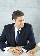 Businessman sitting at table, smiling at colleague