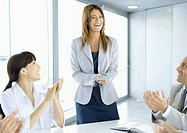 Business team applauding businesswoman