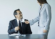 Woman handing mature businessman cup of coffee