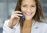 Businesswoman using cell phone, smiling (thumbnail)