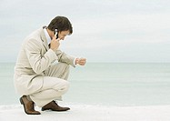 Businessman using cell phone on beach, looking at seashell