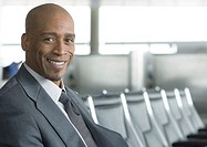 Businessman sitting in airport lounge, smiling at camera
