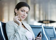 Businesswoman using electronic organizer in airport lounge, smiling at camera