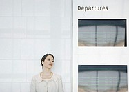 Woman leaning against wall by departure board