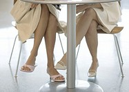 Two women sitting at table, view of legs under table