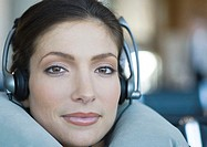 Woman wearing headphones and using neck pillow, close-up (thumbnail)