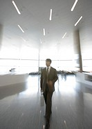 Businessman walking through concourse, blurred motion