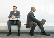 On bench, one businessman sitting with briefcase on lap, second businessman using laptop