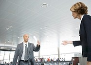 Businessman hurrying to departure gate, holding up ticket