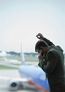 Man phoning, airplane in background