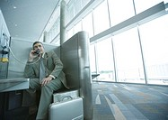 Businessman using pay phone in airport