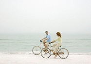 Couple riding bikes on beach
