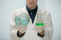 Scientist holding globe and beaker with fluid.