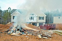 Buring waste at new home site construction rather than taking it to a landfill as required by law