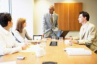 Two businessmen and two businesswomen talking in a conference room