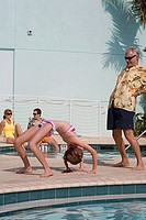 Side profile of a senior man exercising with his granddaughter at poolside