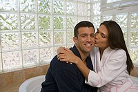 Close-up of a mid adult woman kissing a mid adult man in the bathroom