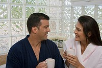 Close-up of a mid adult couple looking at each other and holding cups