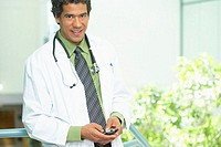 Portrait of a male doctor holding a mobile phone