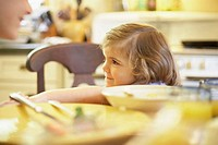 Girl sitting at a dining table and smiling (thumbnail)