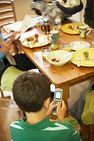 High angle view of a boy sitting at a dining table and using a mobile phone