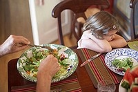High angle view of a girl sitting at a dining table looking displeased