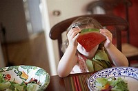 Close-up of a girl holding a slice of watermelon in front of her face