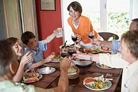High angle view of a family toasting with glasses at a dining table