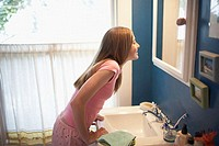 Side profile of a teenage girl looking at a mirror in the bathroom