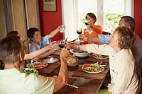 Family toasting with glasses at a dining table