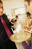 Close-up of a mid adult man pouring champagne into champagne flutes (thumbnail)