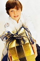 Portrait of a boy holding two Christmas presents (thumbnail)