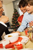 Close-up of grandparents sitting with their grandson at a dining table (thumbnail)